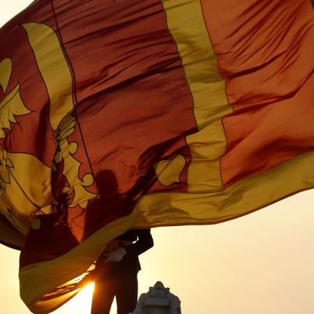 An air force officer holds Sri Lanka's national flag as the sun sets at Galle Face Green in Colombo February 2, 2013. Sri Lankans will celebrate the country's 65th Independence day on February 4 .REUTERS/Dinuka Liyanawatte (SRI LANKA - Tags: POLITICS ANNIVERSARY MILITARY)