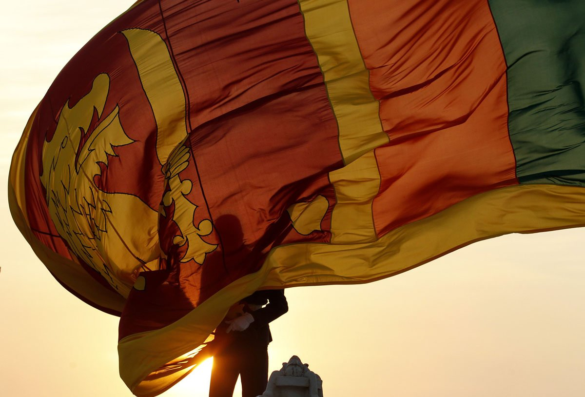 Air force officer holds Sri Lanka's national flag as the sun sets at Galle Face Green in Colombo