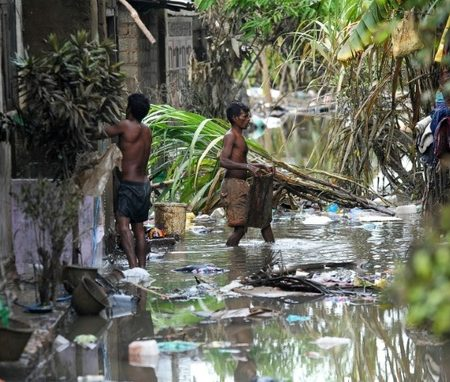 Sri Lankan residents clear debris from outside homes following flooding in the Kolonnawa suburb of Colombo on May 24, 2016 ©Ishara S. Kodikara (AFP)