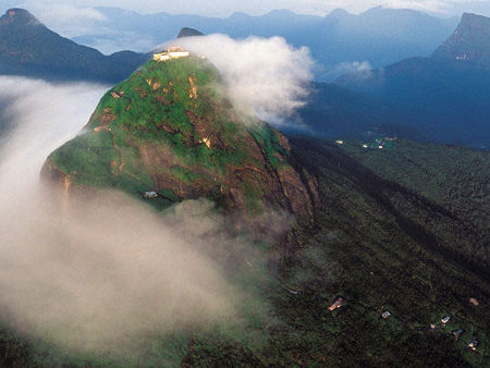 Cloud swirls around the temple on the summit of Adam's Peak by Dominic Sansoni