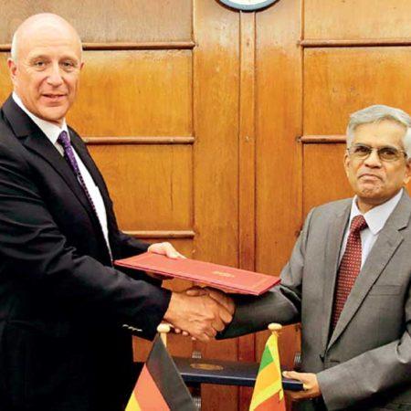Finance Ministry Secretary Dr. R.H.S. Samaratunga and German Ambassador to Sri Lanka Dr. Jürgen Morhard shake hands after signing the agreement